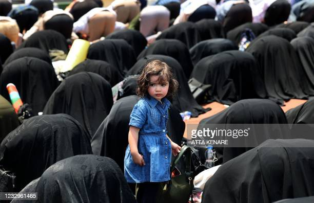 Girl looks on as Iranians pray during a protest to condemn the ongoing Israeli air campaign on Gaza at Palestine Square in central Tehran, on May 18,...