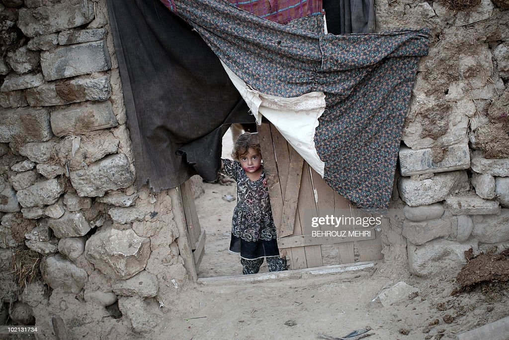 A girl looks on as she stands on the doorstep of her house in an Afghan and Pakistani slum area in Islamabad on June 15, 2010. Pakistan approached the International Monetary Fund in 2008 and has secured a 11.3 billion USD standby loan in an effort to contain inflation and cope with a rapid depletion of reserves that were barely enough to cover nine weeks of import bills.