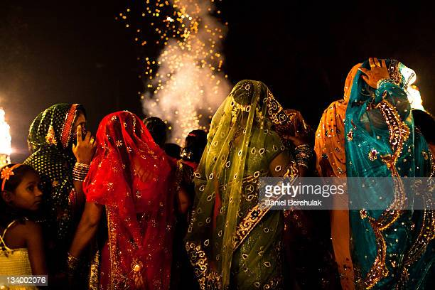 A girl looks on as women dressed in saris accompany a wedding procession on November 23 2011 in New Delhi India India's wedding season peaks from...