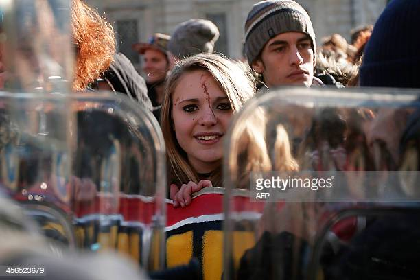 Girl looks on during a protest by students against the local government in downtown Turin on December 14, 2013. Protesters clashed with police during...
