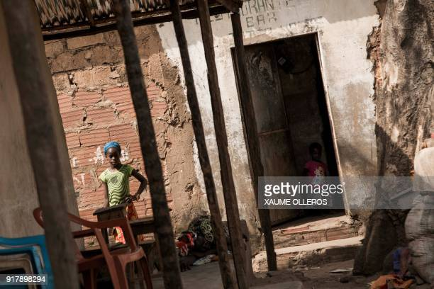 A girl looks on in the Mindara neighbourhood in Bissau on Mardi Gras on February 13 2018 / AFP PHOTO / Xaume Olleros