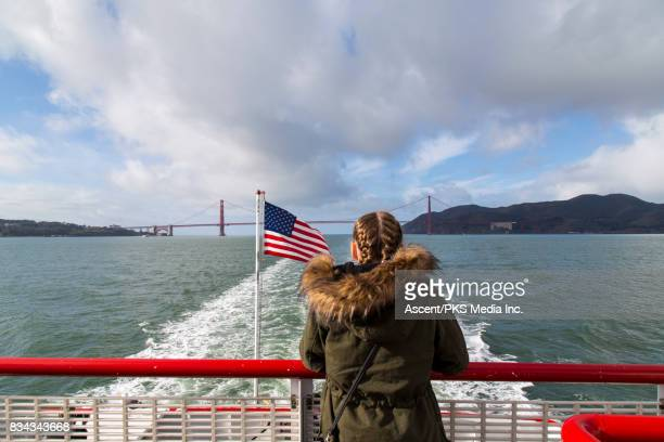 Girl looks out from boat stern during bay crossing