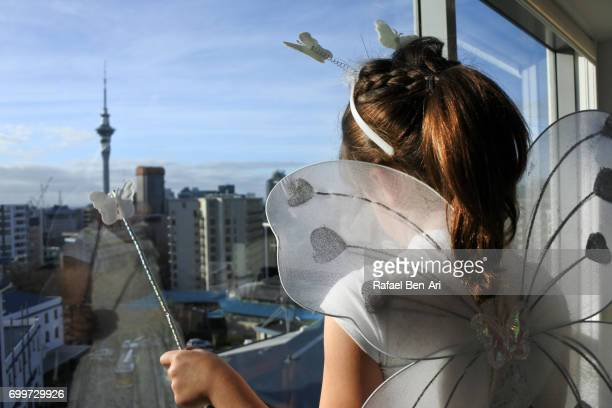 Girl looks out of a window overlooking a city landscape