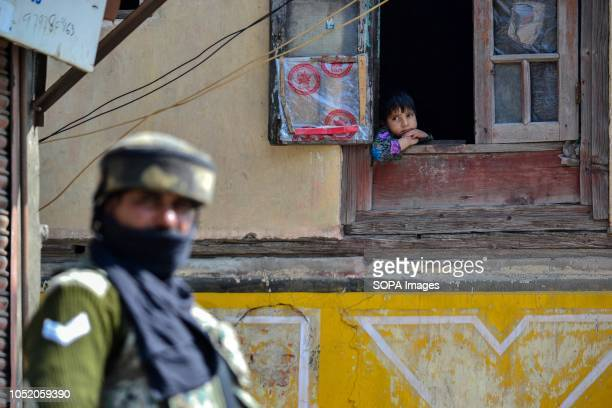 A girl looks out of the window as a paramilitary trooper stands guard outside the polling station during the third phase of local elections in...