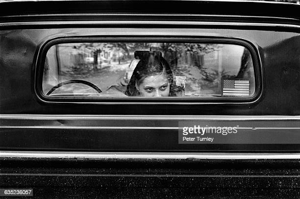 A girl looks out the back window of a truck cab on McClellan Street which is located in a racially diverse working class neighborhood A sticker of an...