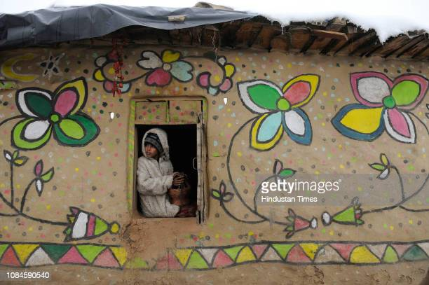 A girl looks outside from her mud house as she warms her hands on a fire pot on the outskirts of Srinagar on January 18 2019 in Srinagar India