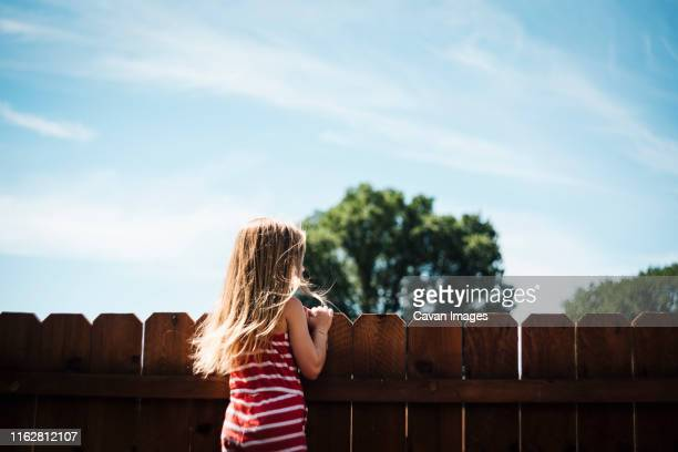 girl looks over fence in backyard on a sunny summer day - great plains stock pictures, royalty-free photos & images