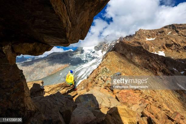 a girl looks the wild landscape. corna rossa pass, valmalenco, valtellina, lombardy, italy, europe. - italia stock-fotos und bilder