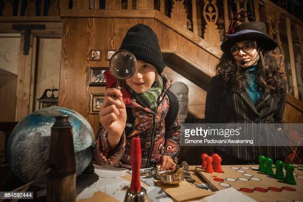 A girl looks through a magnifying glass of Santa Claus in his house in the Reggia of Venaria on December 2 2017 in Turin Italy