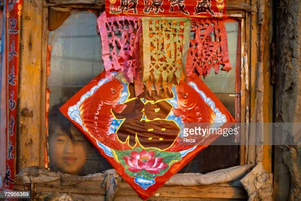 A girl looks through the window of her house decorated traditionally for Chinese New Year on February 1999 in Mohe China
