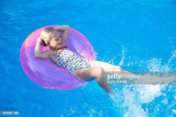 Girl lying back on inflatable ring in garden swimming pool
