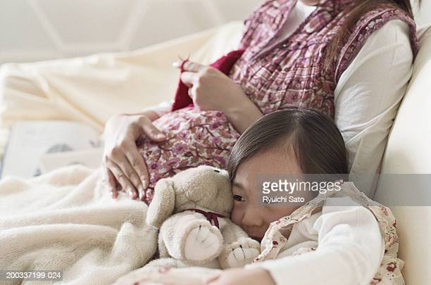 Girl (4-5) lying by pregnant woman on sofa, close-up
