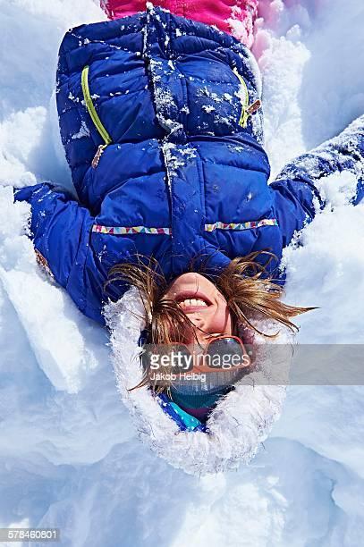 Girl lying down in snow, Chamonix, France
