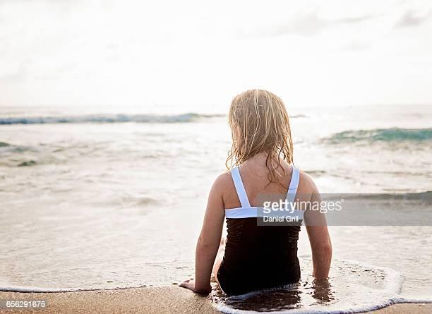 Girl (4-5) lying down in water on beach