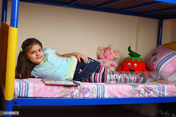 Girl lying down on a bunker bed and reading