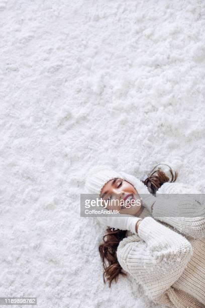 mädchen liegt auf dem schnee - lying down stock-fotos und bilder