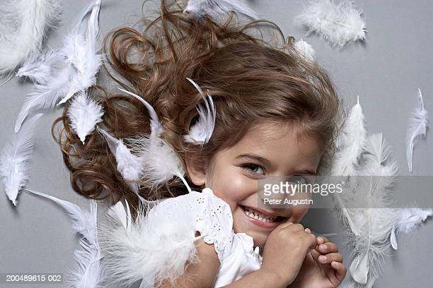 Girl (2-4) lying down on white feathers, smiling, portrait, close-up
