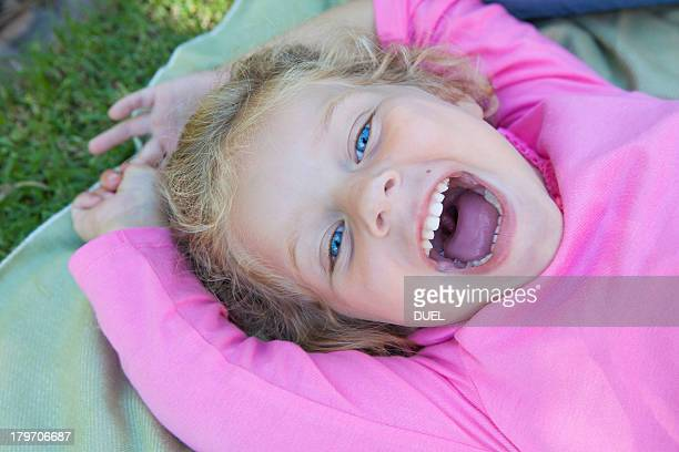 girl lying down with mouth open, smiling - girls open mouth stockfoto's en -beelden