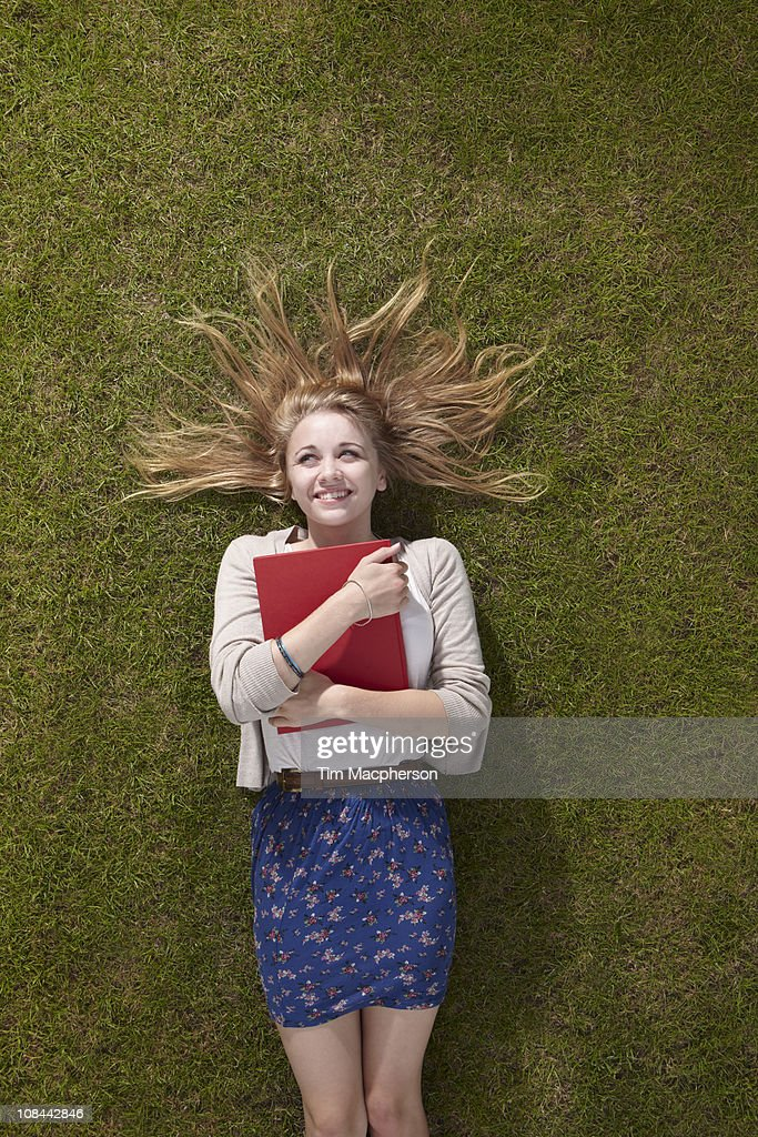 Girl lying holding a book : Stock Photo