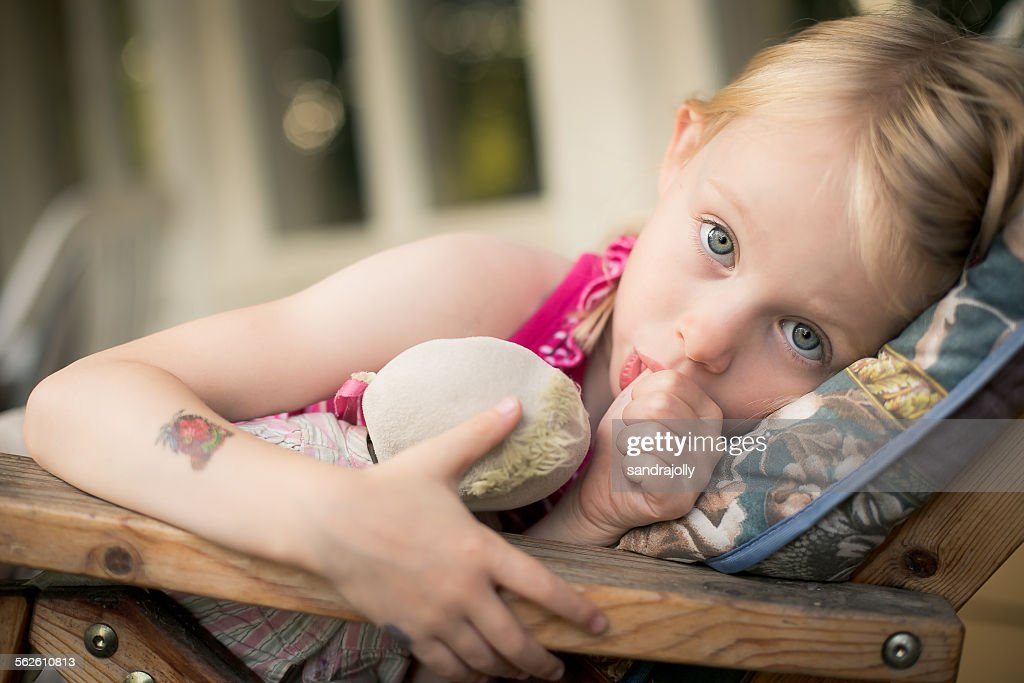 Girl lying in a chair sucking her thumb : Stock Photo