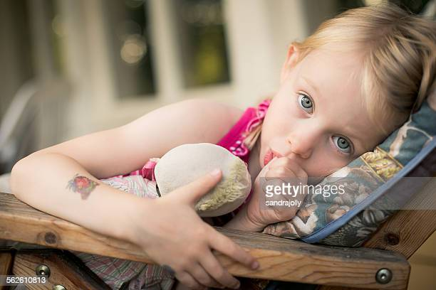 Girl lying in a chair sucking her thumb
