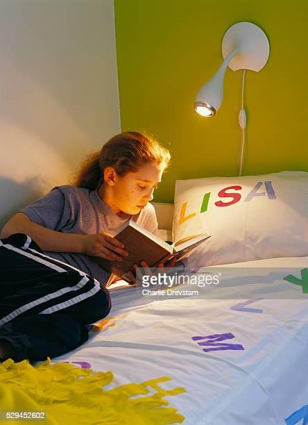Girl lying in bed reading