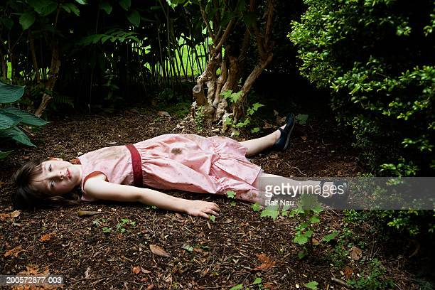 girl (3-5) lying in garden - female corpse stock photos and pictures