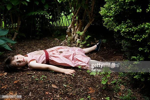 Girl (3-5) lying in garden
