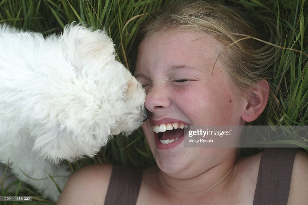 Girl (10-12) lying in grass, puppy licking face, laughing