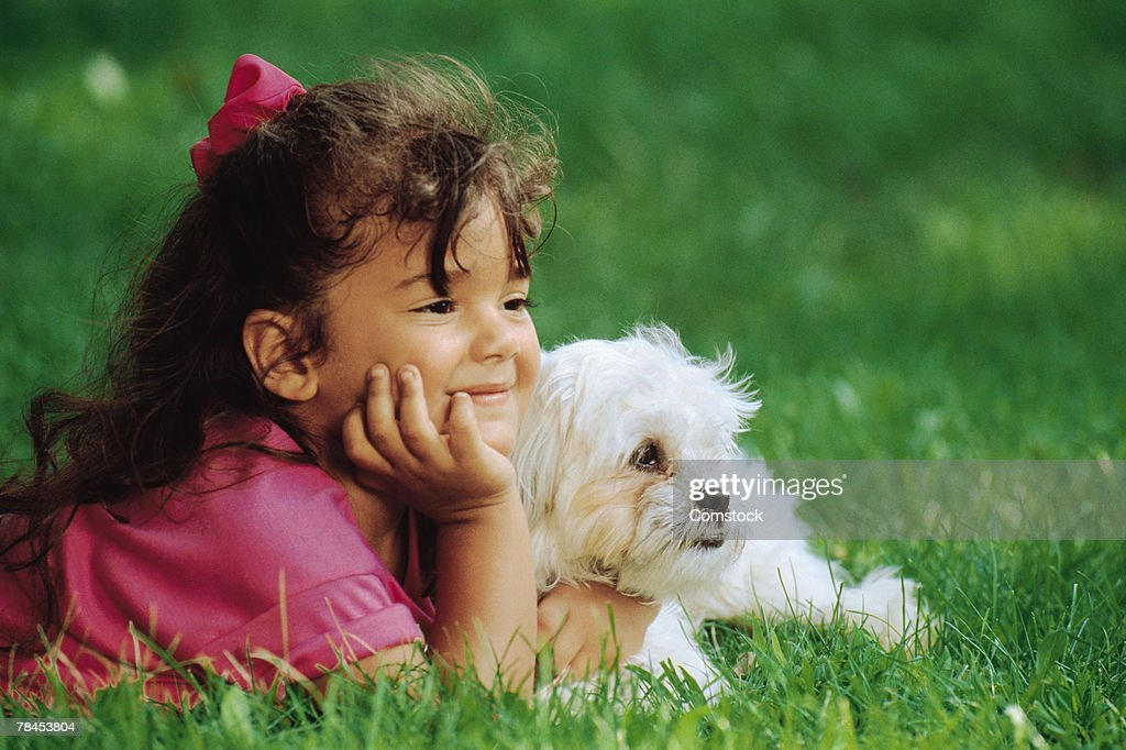 Girl lying in grass with dog : Stockfoto