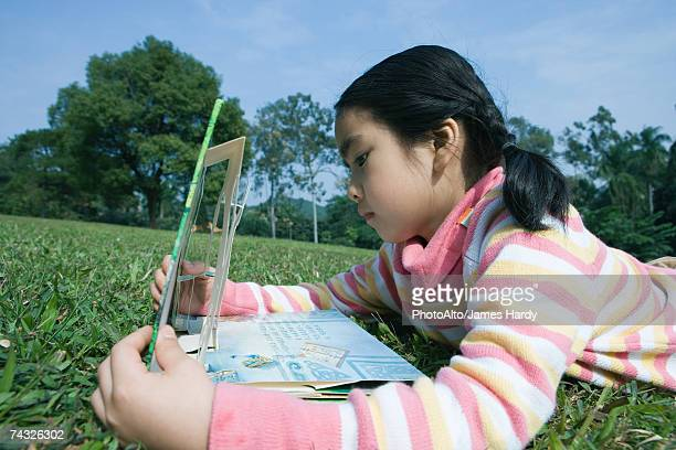 girl lying in grass with pop-up book - pop up book stock pictures, royalty-free photos & images