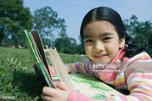 Girl lying in grass with pop-up book