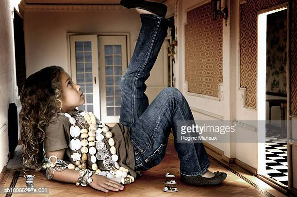 Girl (6-7 years) lying in miniature room, side view