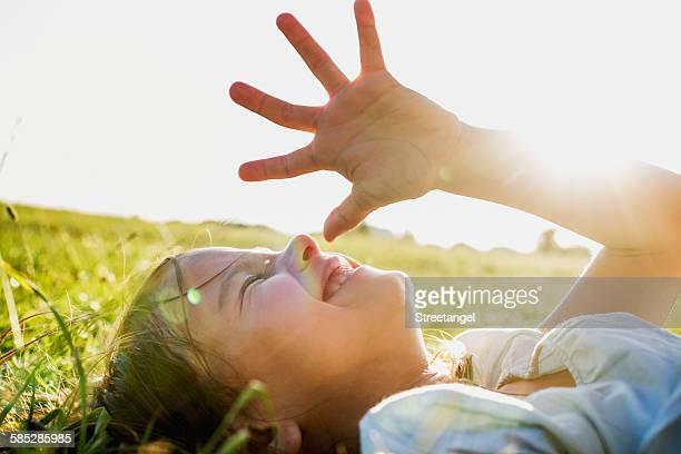 Girl lying in park shielding eyes from sunlight