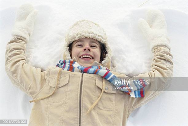 Girl (10-12) lying in snow, making snow angel, elevated view