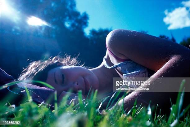 Girl lying in the grass UK 2005