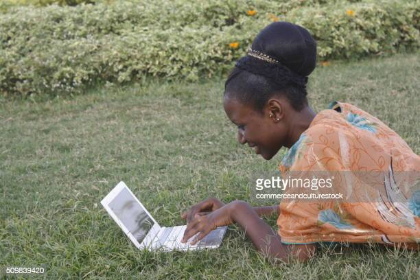 A girl lying in the grass with a laptop