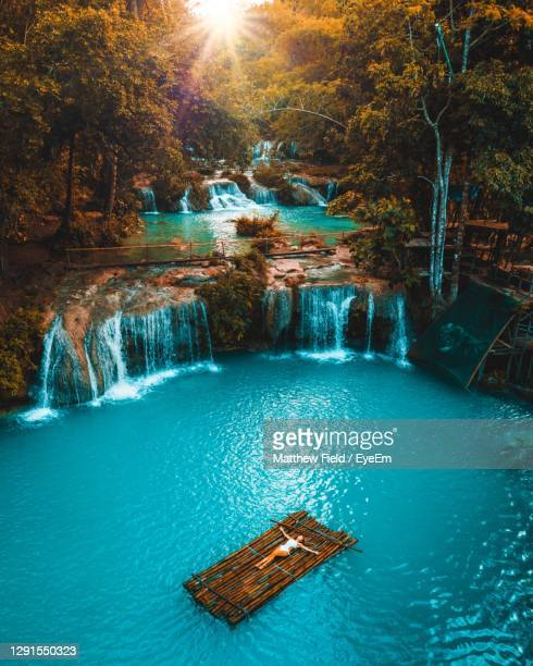 girl lying on a bamboo raft in the middle if a waterfall in the philippines - paisajes de filipinas fotografías e imágenes de stock