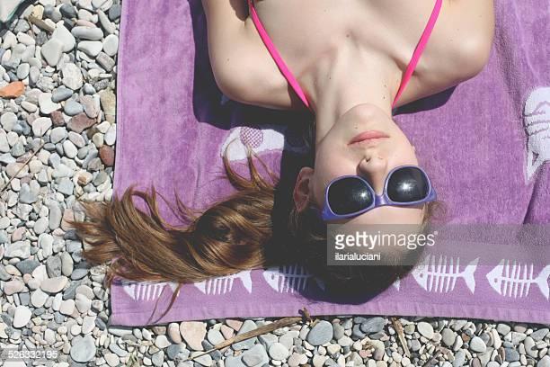 girl lying on a blanket sunbathing - girls sunbathing stock photos and pictures