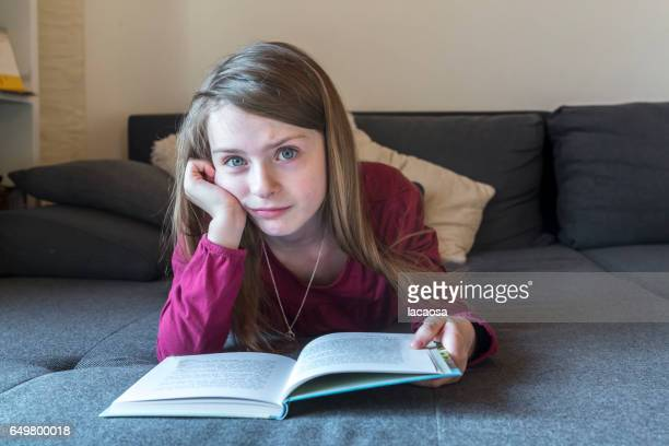girl lying on a sofa and reading a book