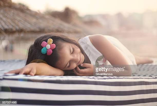 Girl lying on a sun lounger at the beach