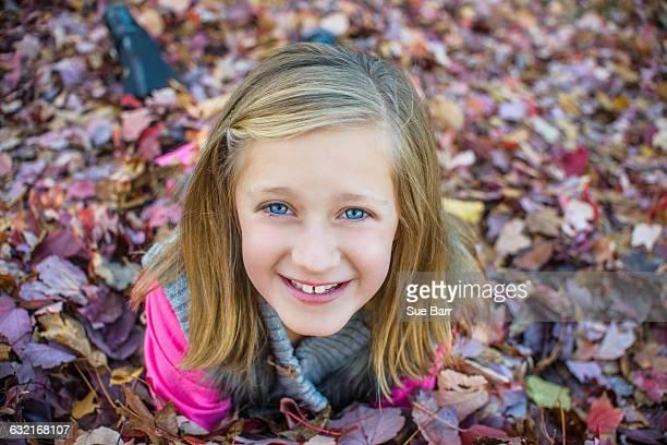 Girl lying on autumn leaves in garden
