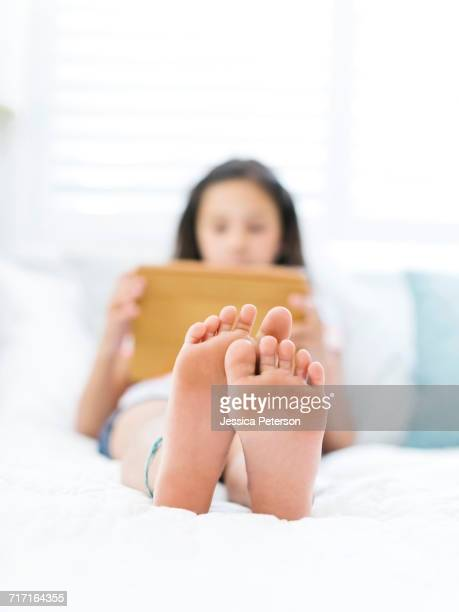 Girl (10-11) lying on back and using tablet with naked feet in foreground