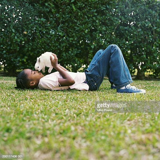 Girl (8-10) lying on back in grass, holding white bunny to nose