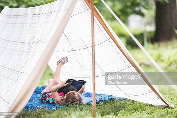 Girl lying on back in homemade garden tent looking at digital tablet
