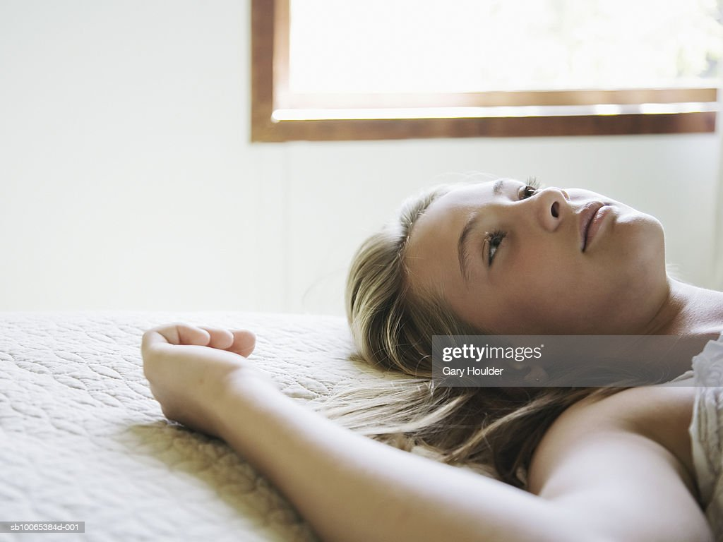 Girl (12-13) lying on bed, close-up : Foto stock