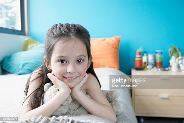 Girl (7-8) lying on bed, smiling, portrait