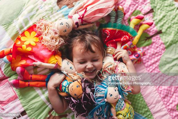 Girl lying on bed surrounded by rag dolls