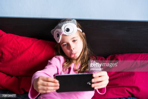 girl lying on bed taking selfie with cell phone - nur kinder stock-fotos und bilder