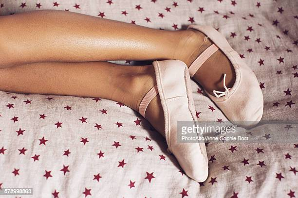 Girl lying on bed, wearing ballet slippers, cropped